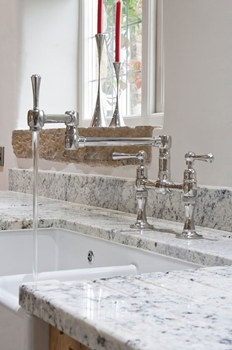 Hornbeam Ivy bridge mixer tap with articulated spout. Work surfaces in Delicatus cream granite.